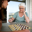 Stock Photo: Young womand senior womplaying checkers