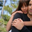 Serious couple embracing in a park - Photo