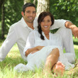 Couple in white sitting on the grass - Stock Photo