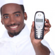 Smiling afro-American caterer with telephone, studio shot - Stok fotoğraf