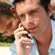 Boy embracing his father while he is talking on his cell — Stock Photo
