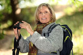 Fair-haired elderly woman with binoculars — Stock Photo