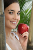 Woman eating a red apple amongst bamboo — Stock Photo