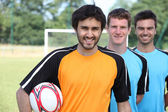 Three footballers in a line-up in front of goal — Stock Photo