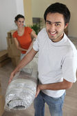 Couple carrying carpet — Stock Photo