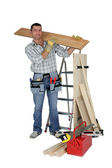 A handyman carrying a wooden plank — Stock Photo