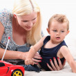 Stock Photo: Young mother with her son and remote controlled car
