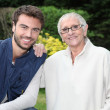 Smiling young man and older woman in garden — Stock fotografie