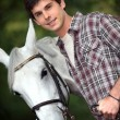 Closeup of young man with a white horse — Stock Photo #8907879