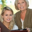 Senior and her granddaughter looking at photos — Stock fotografie