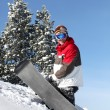 Stock Photo: Snowboarder struggling to drag his board up mountain