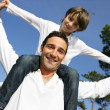Father carrying his son on his shoulders — Stock Photo #8909698