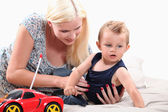 Young mother with her son and a remote controlled car — Stock Photo