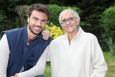 Smiling young man and older woman in garden — Stock Photo
