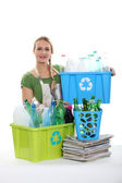 A woman recycling plastic bottles. — Stock Photo