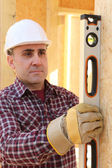 Builder checking wall's verticality with a level tube — Stock Photo