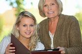 Senior e sua neta olhando fotos — Foto Stock