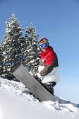 сноубордист, изо всех сил тащить его правления в гору — Стоковое фото
