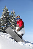 Snowboarder struggling to drag his board up the mountain — Photo