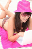 Young woman using her laptop computer on the beach — Stock Photo