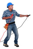 Manual worker with a set of jump leads — Stock Photo
