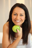 Portrait of a smiling woman with a Granny Smith apple — Stock Photo