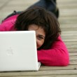 Brunette laying on jetty with computer — Stock Photo #8911143