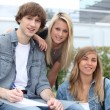 Three young students smiling at us on a campus. — Stock Photo