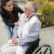 A young woman helping a senior woman in wheelchair — Stock Photo