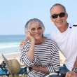 Senior couple riding bikes by the beach — Stock Photo