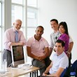 Group of colleagues gathered around computer - Stock Photo