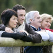 Two couples leaning on a countryside fence — Stock Photo