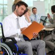 A group of business in a meeting room, one of them in a wheelchair. — Stock Photo