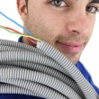 Electrician with a reel of wires - Stock Photo