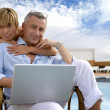 Couple using a laptop by the poolside - 