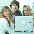 Teenagers sitting round a laptop computer — Stock Photo #8917852