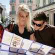 Couple reading plan downtown - 