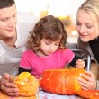 Stock Photo: Family carving pumpkin