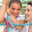 Stock Photo: A little girl and her mother playing in a playground