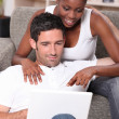 Mixed couple surfing the net — Stock Photo