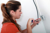 Female electrician installing a power point — Stock Photo