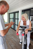 Man timing his wife's workout — Stock Photo