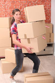 Woman struggling to carry boxes — Stock Photo