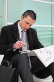 A young businessman looking newspaper — Stock Photo
