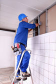 Construction worker panelling wall — Stock Photo