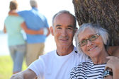 Relaxed older couple sitting in the shade of a tree on a summer's day — Stock Photo