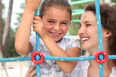 A little girl and her mother playing in a playground — Stock Photo