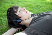Teenager lying on grass listening to music — Stock Photo