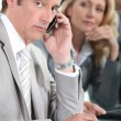 Male executive on cellphone during meeting — Stock Photo