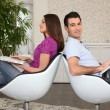 Stock Photo: Couple using laptops in matching chairs